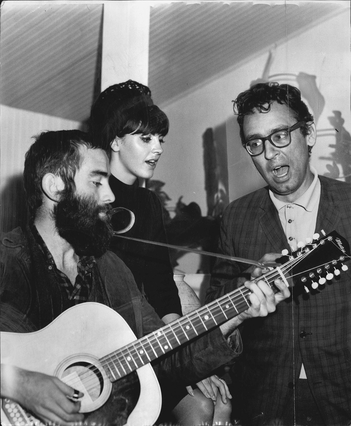 The American folk singer Dr. L. Gottlieb (right) joins Australian folk singers Frank Povah and Tina Date in an impromptu concert after his arrival at Kingsford Smith Airport yesterday, from the United States. Dr. Gottlieb is in Australia for a series of c